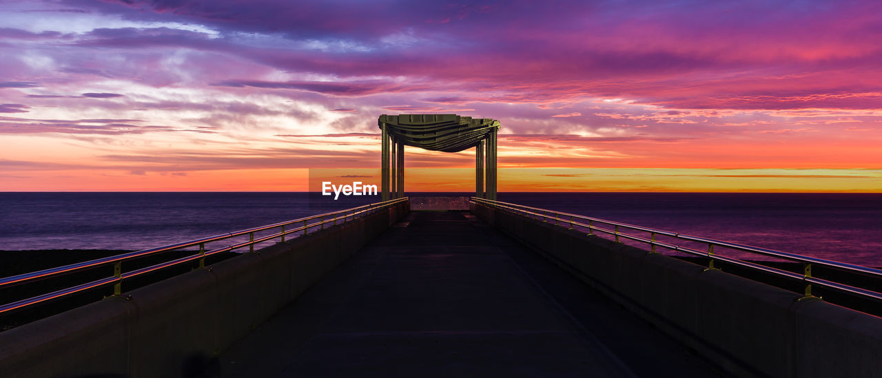 sunset, sea, sky, water, horizon over water, built structure, cloud - sky, the way forward, bridge - man made structure, architecture, beauty in nature, railing, connection, travel destinations, scenics, outdoors, tranquil scene, nature, suspension bridge, tranquility, no people, beach, horizon, day