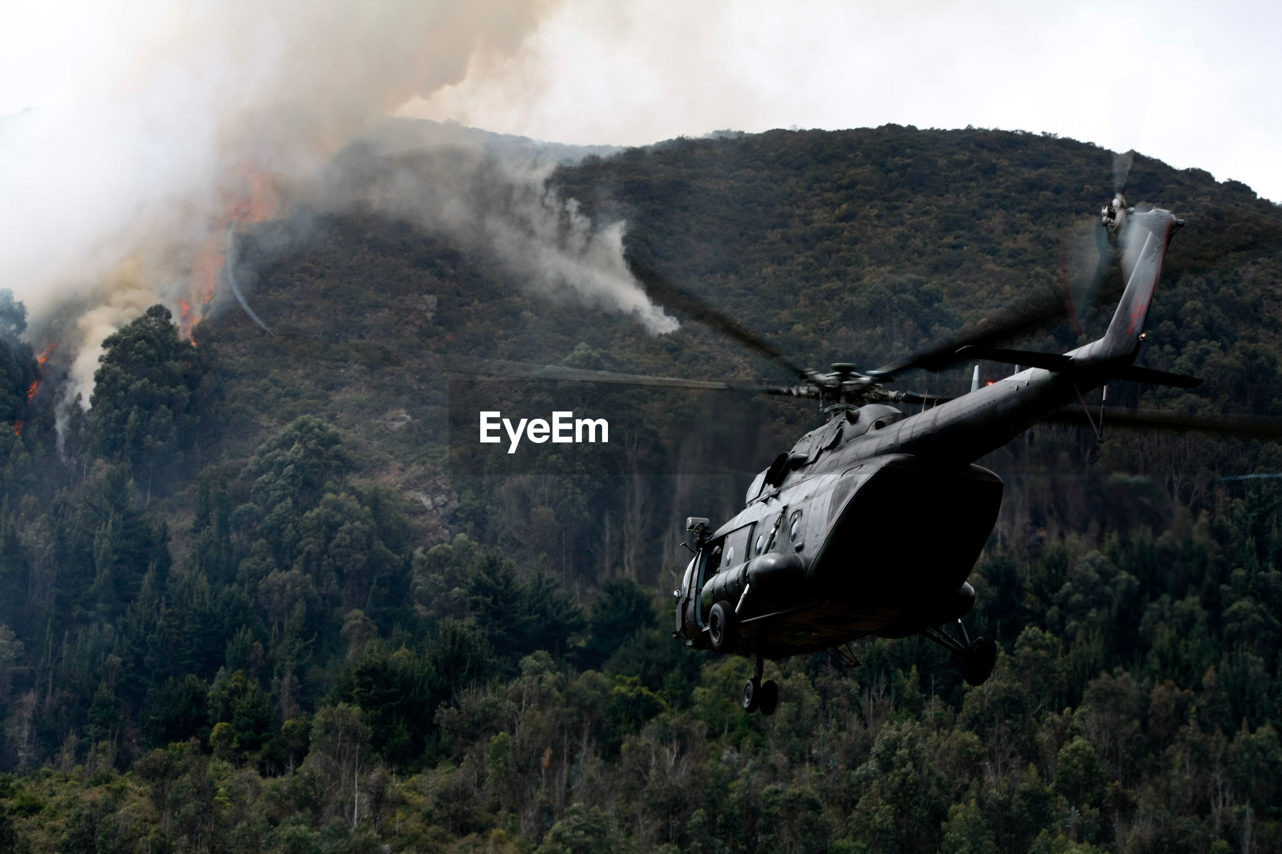 Helicopter flying against fire on mountain