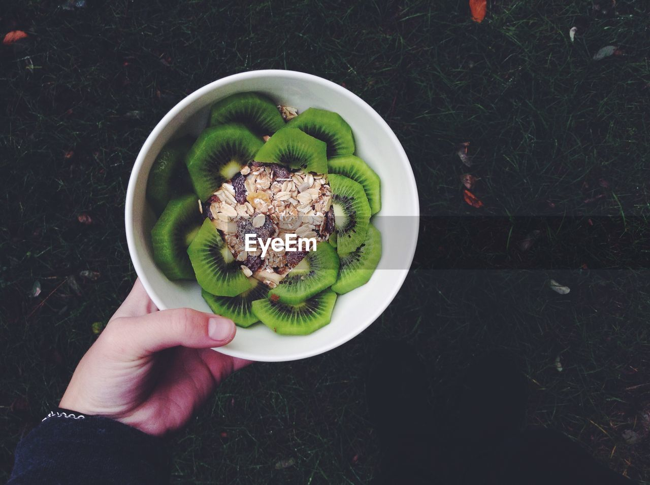 Cropped image of hand holding bowl of kiwi with breakfast cereals