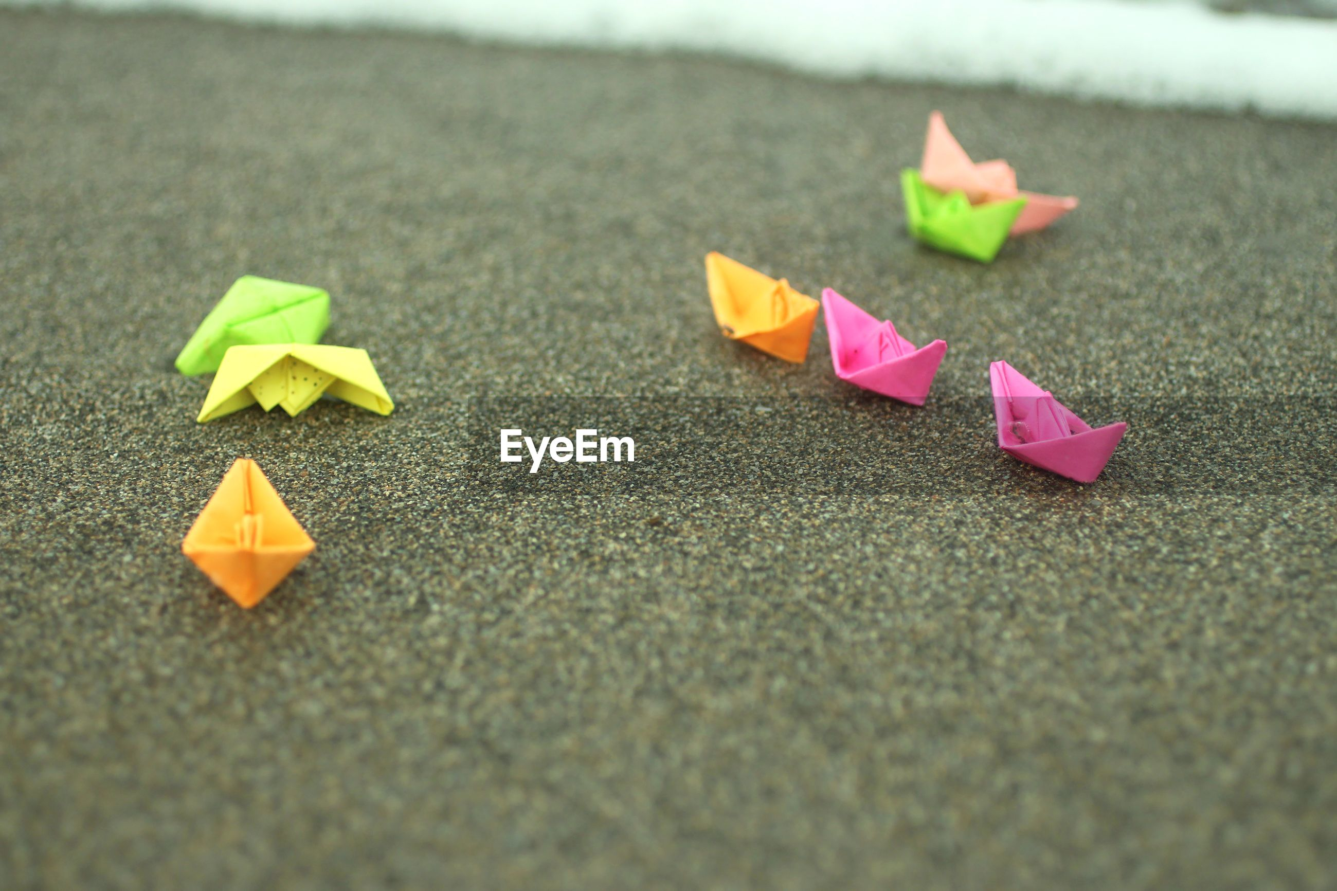 Close-up of origami paper boat on sand at beach