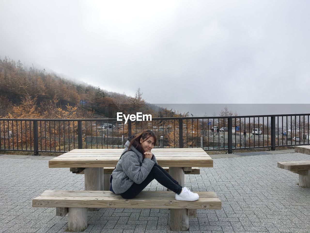 Portrait of woman sitting on bench against sky
