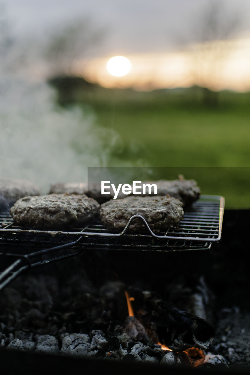Food on barbecue against field
