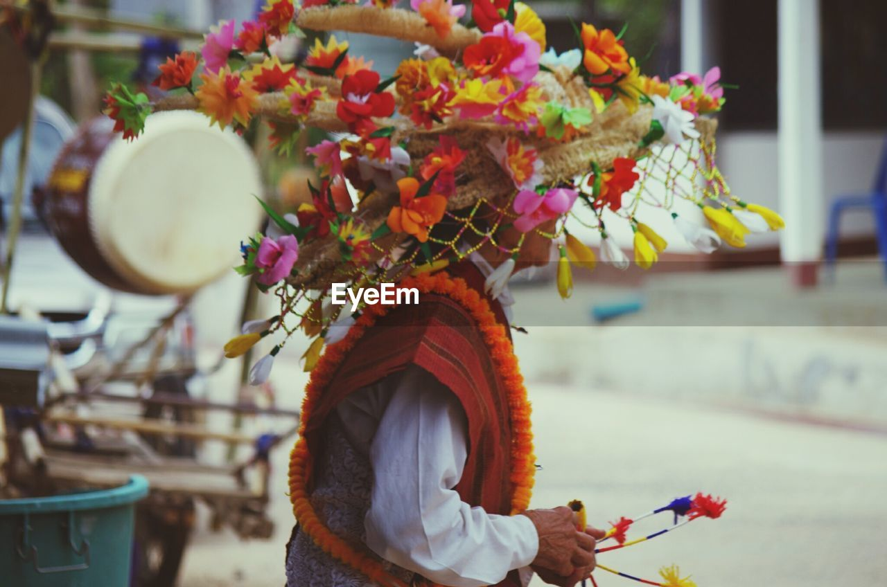 one person, focus on foreground, real people, flower, clothing, flowering plant, holding, plant, lifestyles, adult, celebration, belief, day, religion, women, traditional clothing, nature, life events, wedding ceremony