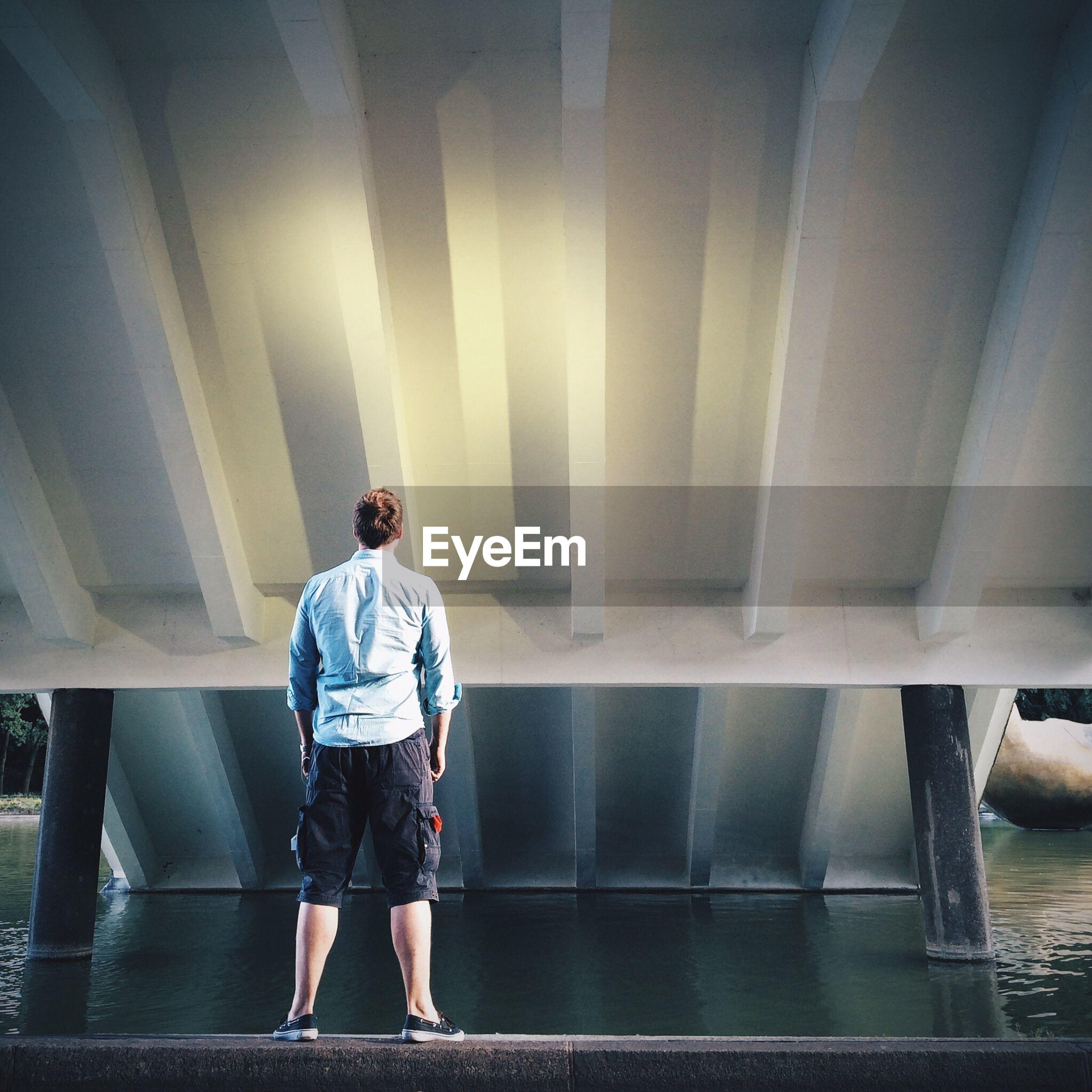 Rear view of man standing on wall by lake below bridge