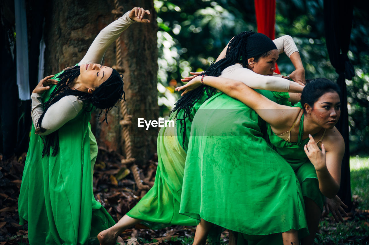 traditional clothing, cultures, dancing, real people, green color, performance, young women, leisure activity, day, standing, outdoors, togetherness, traditional dancing, young adult, friendship