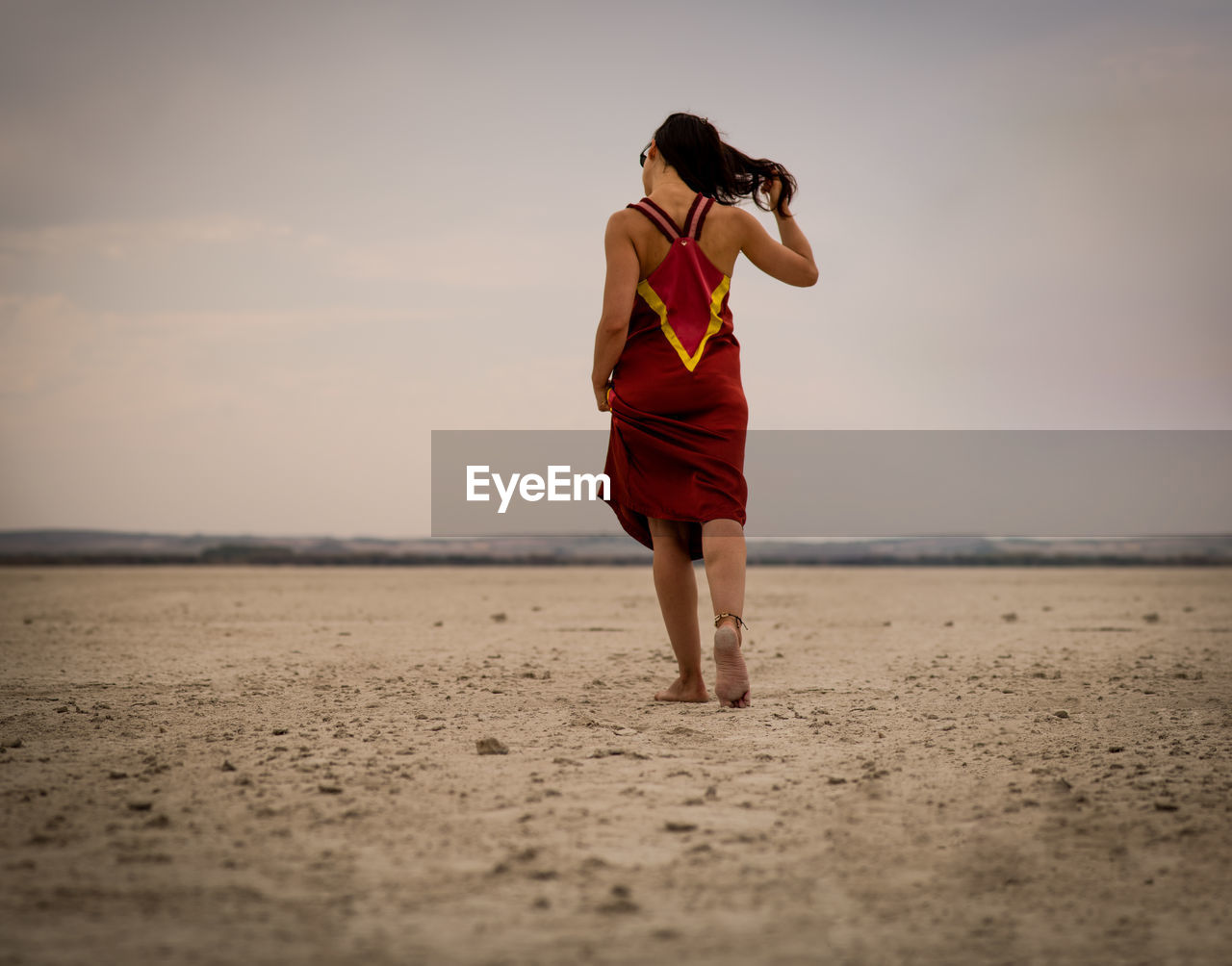 land, sky, one person, real people, lifestyles, full length, leisure activity, beach, sand, women, adult, standing, nature, scenics - nature, beauty in nature, young adult, tranquility, environment, desert, outdoors, beautiful woman, climate, arid climate