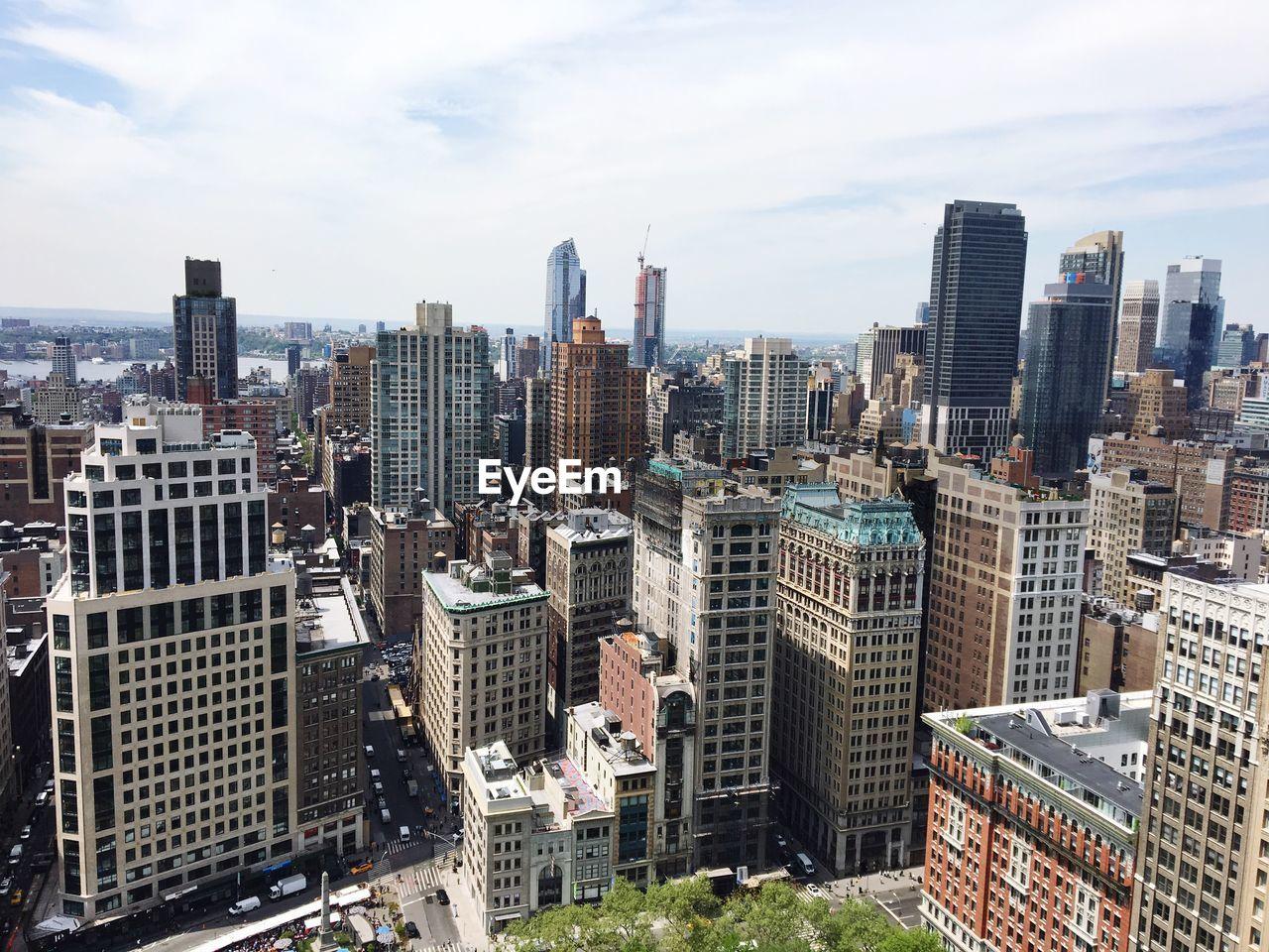 High Angle View Of Urban Skyline Against Cloudy Sky