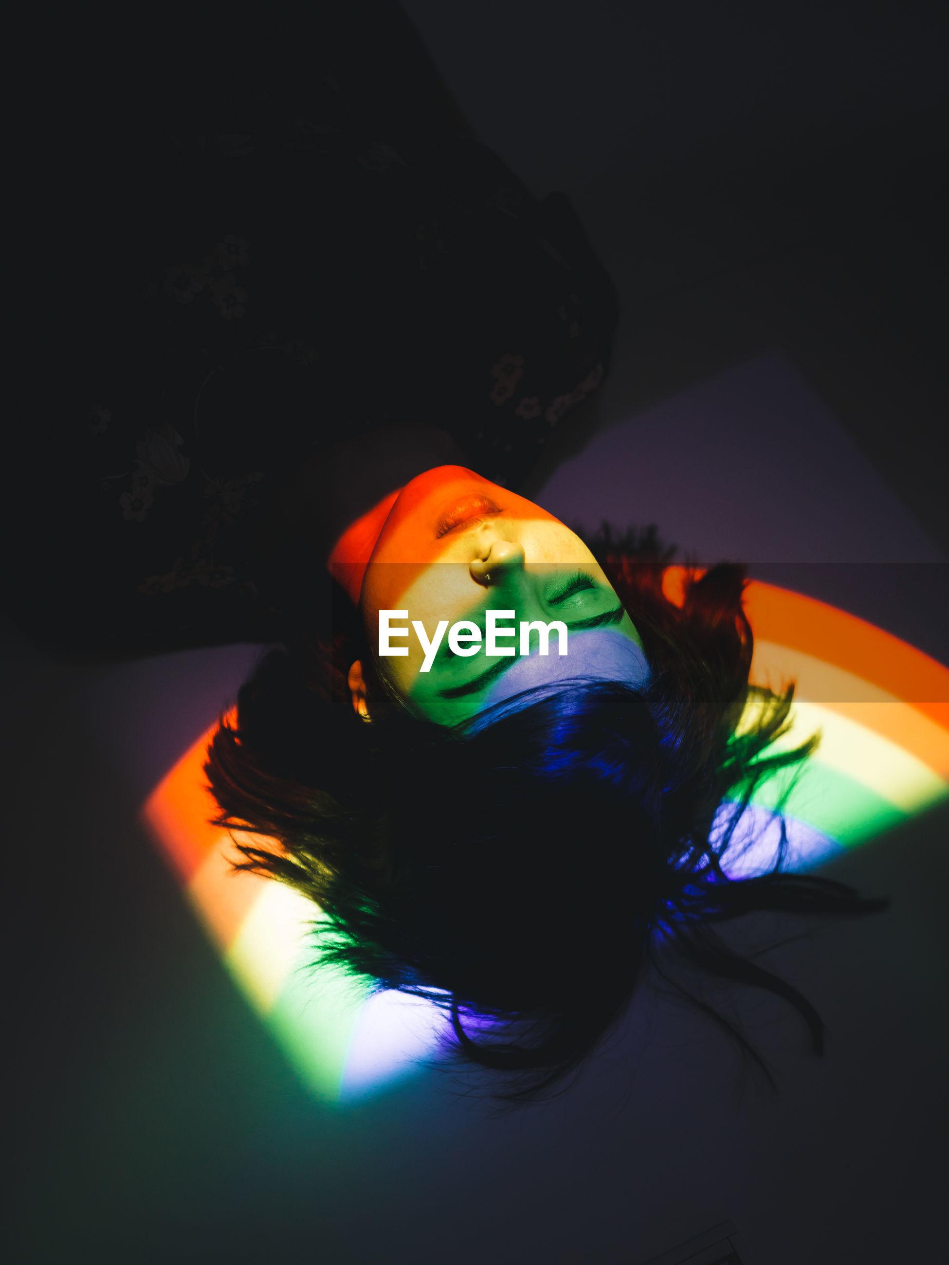 High angle view of rainbow light falling on woman sleeping at home