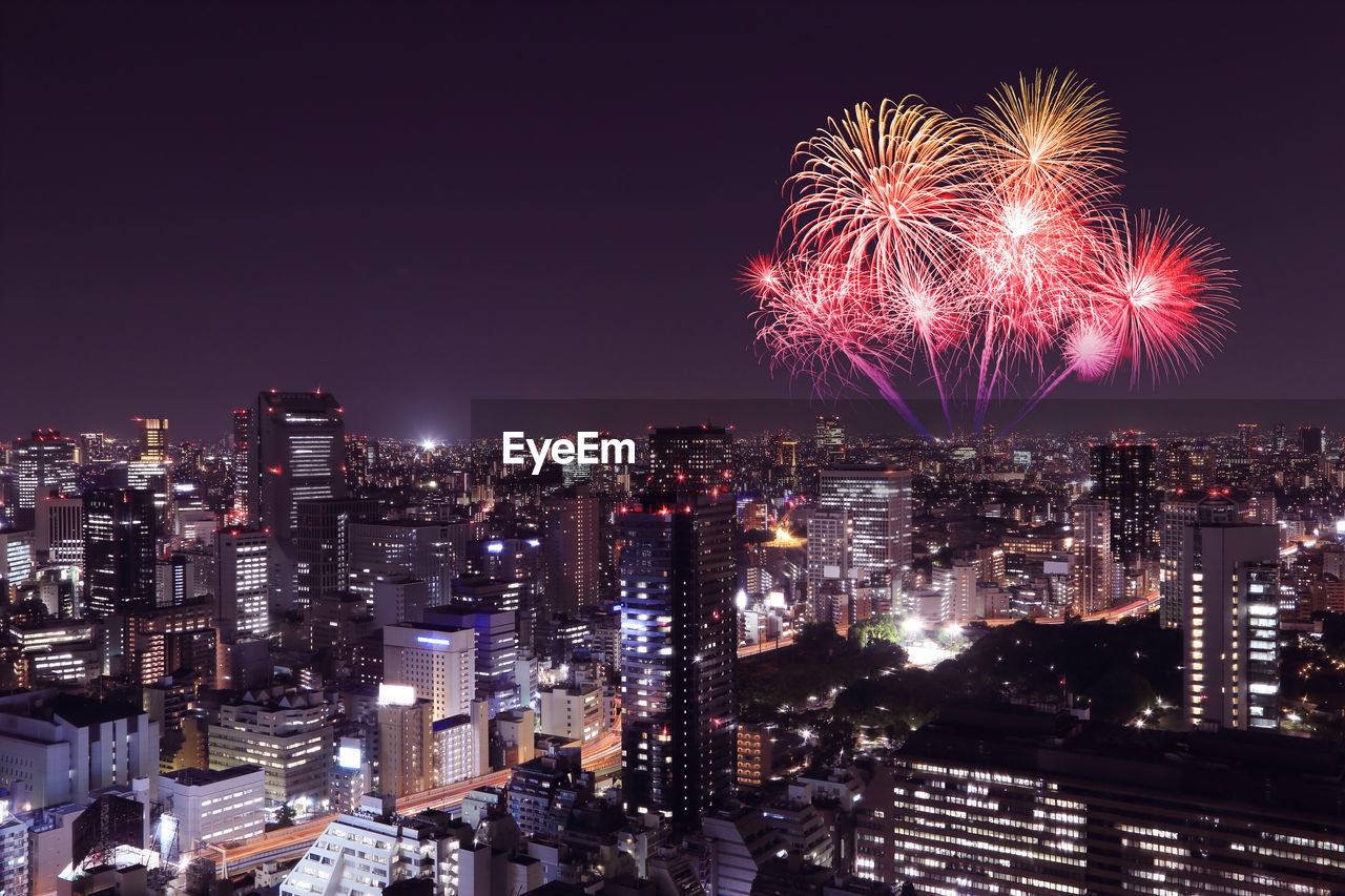 illuminated, night, building exterior, architecture, cityscape, city, firework, motion, built structure, celebration, event, firework display, sky, arts culture and entertainment, exploding, building, no people, glowing, nature, long exposure, office building exterior, firework - man made object, light, outdoors, skyscraper