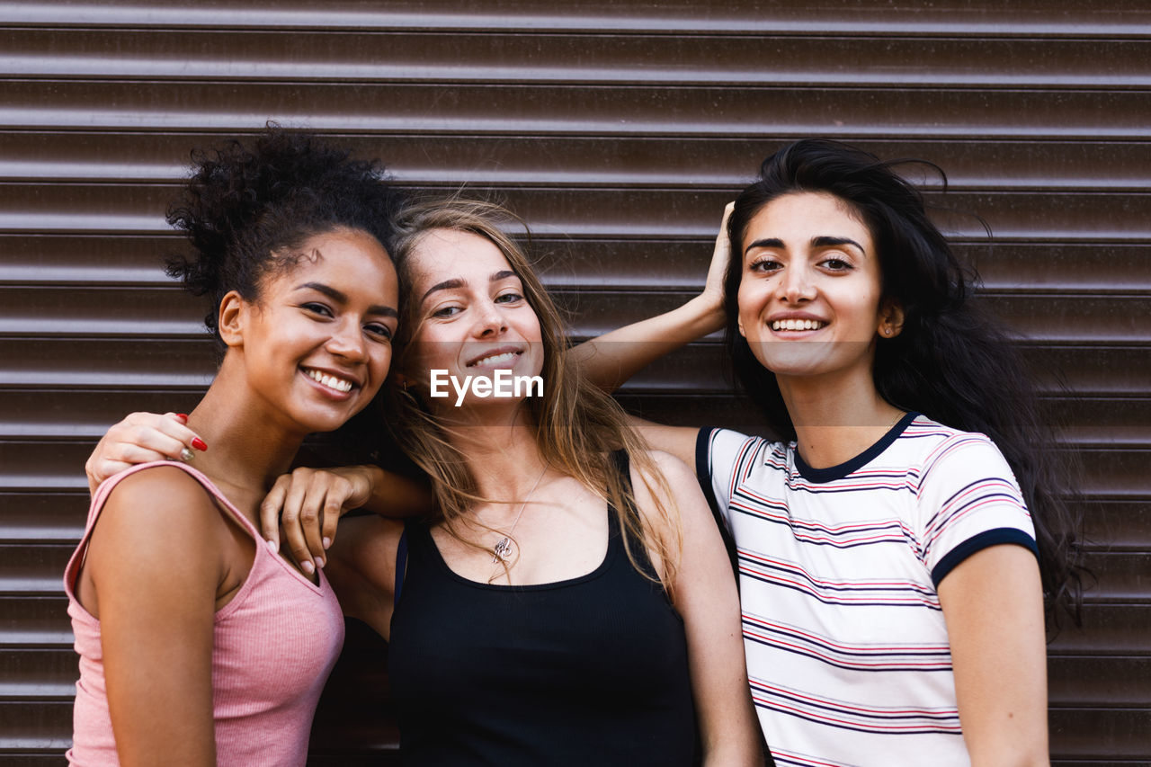Portrait Of Female Friends Smiling While Standing By Closed Shutter
