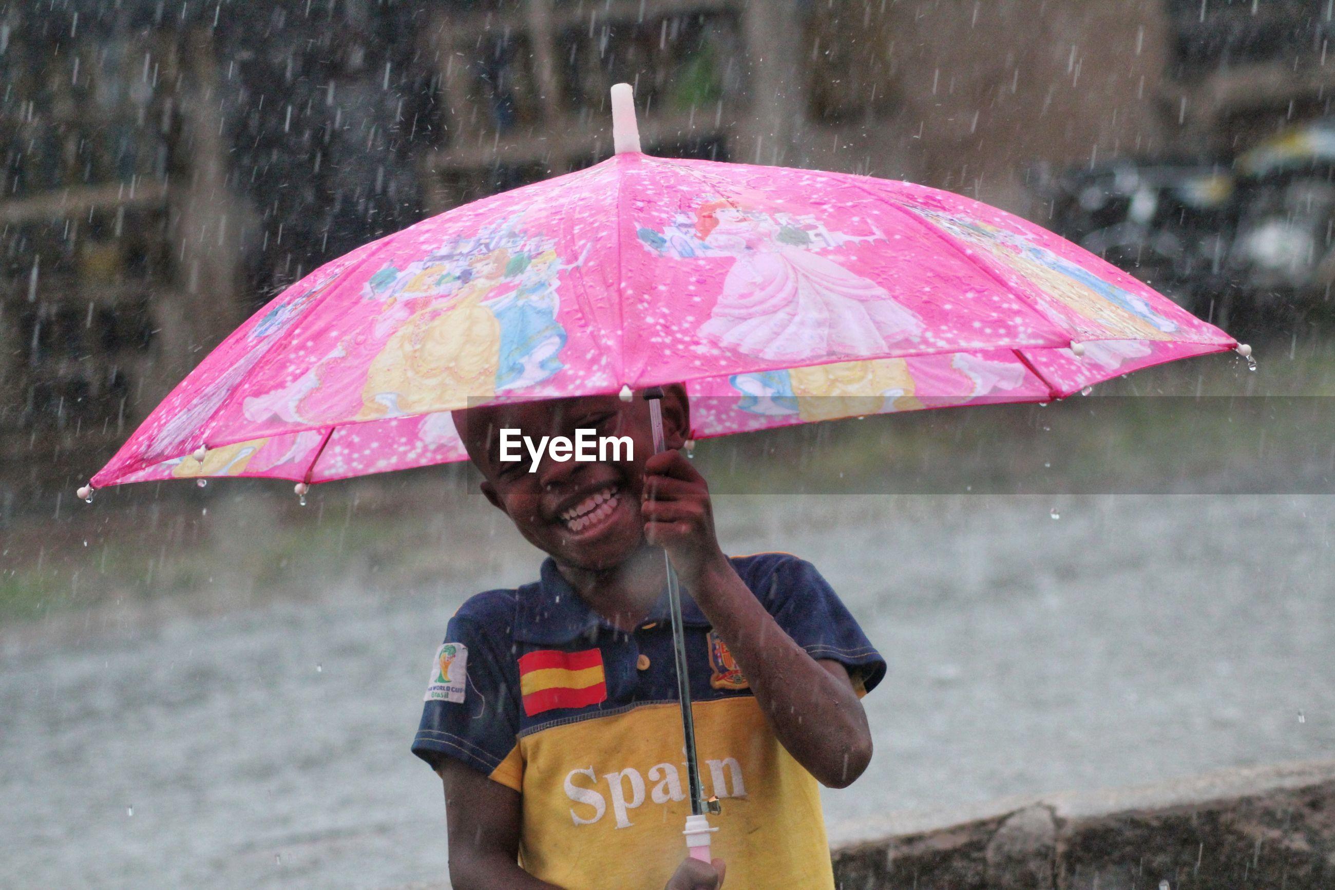 Happy boy holding umbrella during rainy season
