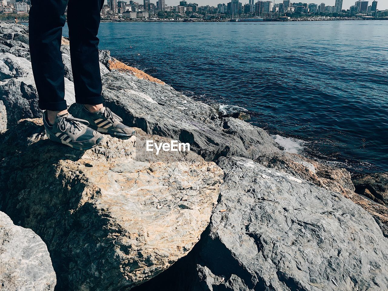 Low section of person standing on rock by sea