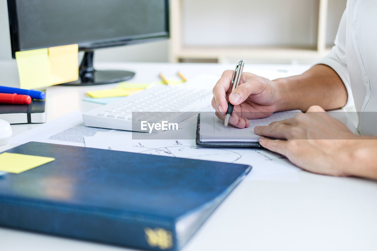Midsection Of Business Person Writing On Diary At Desk In Office