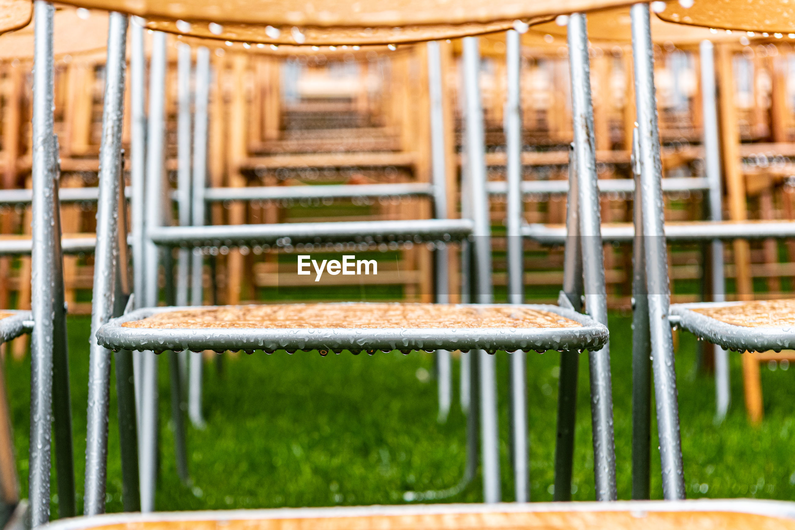 Lot of wooden chairs stand outside in the park in the rain. empty auditorium, grass, water drops.