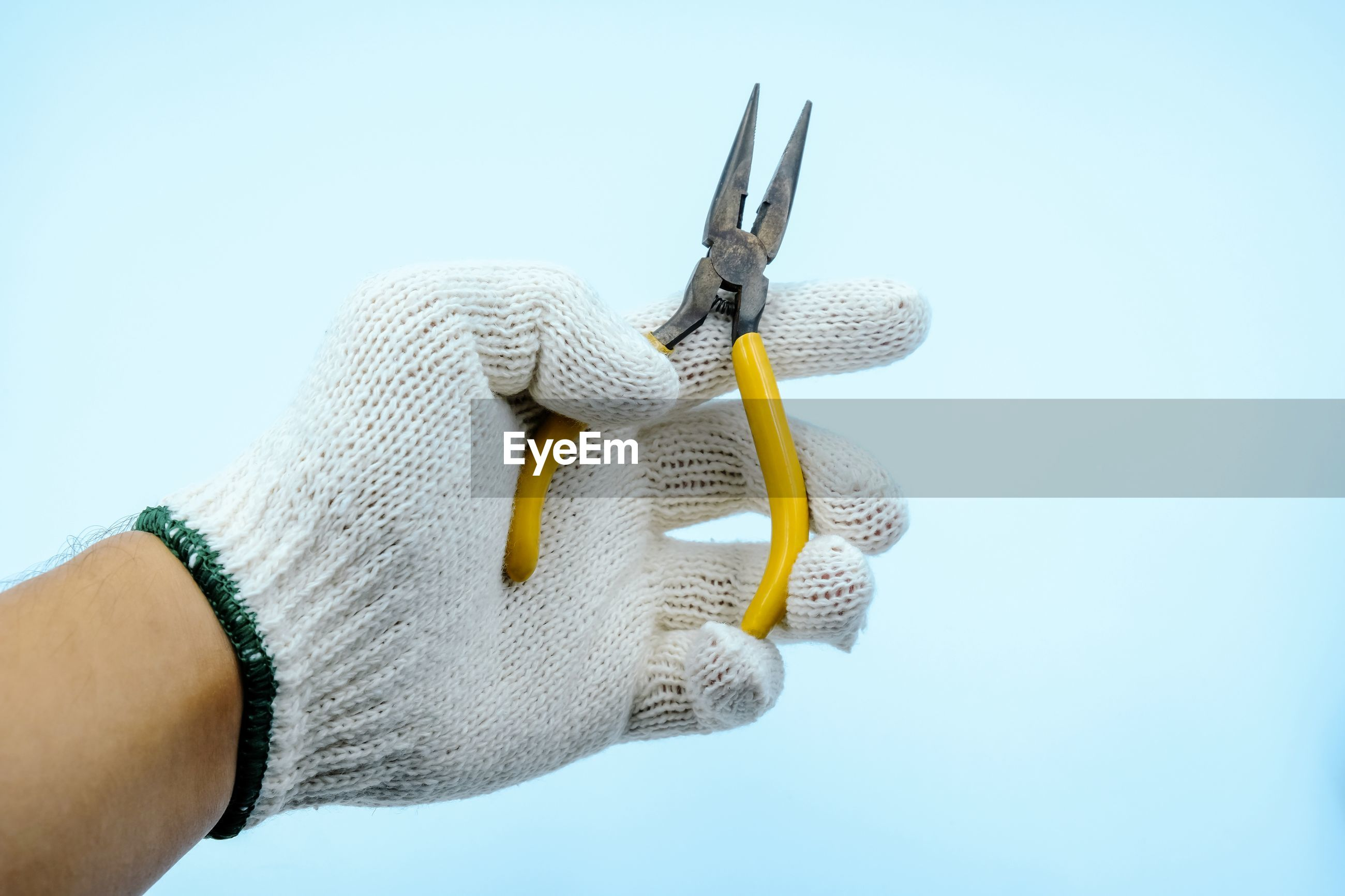 Close-up of hand holding pliers against white background