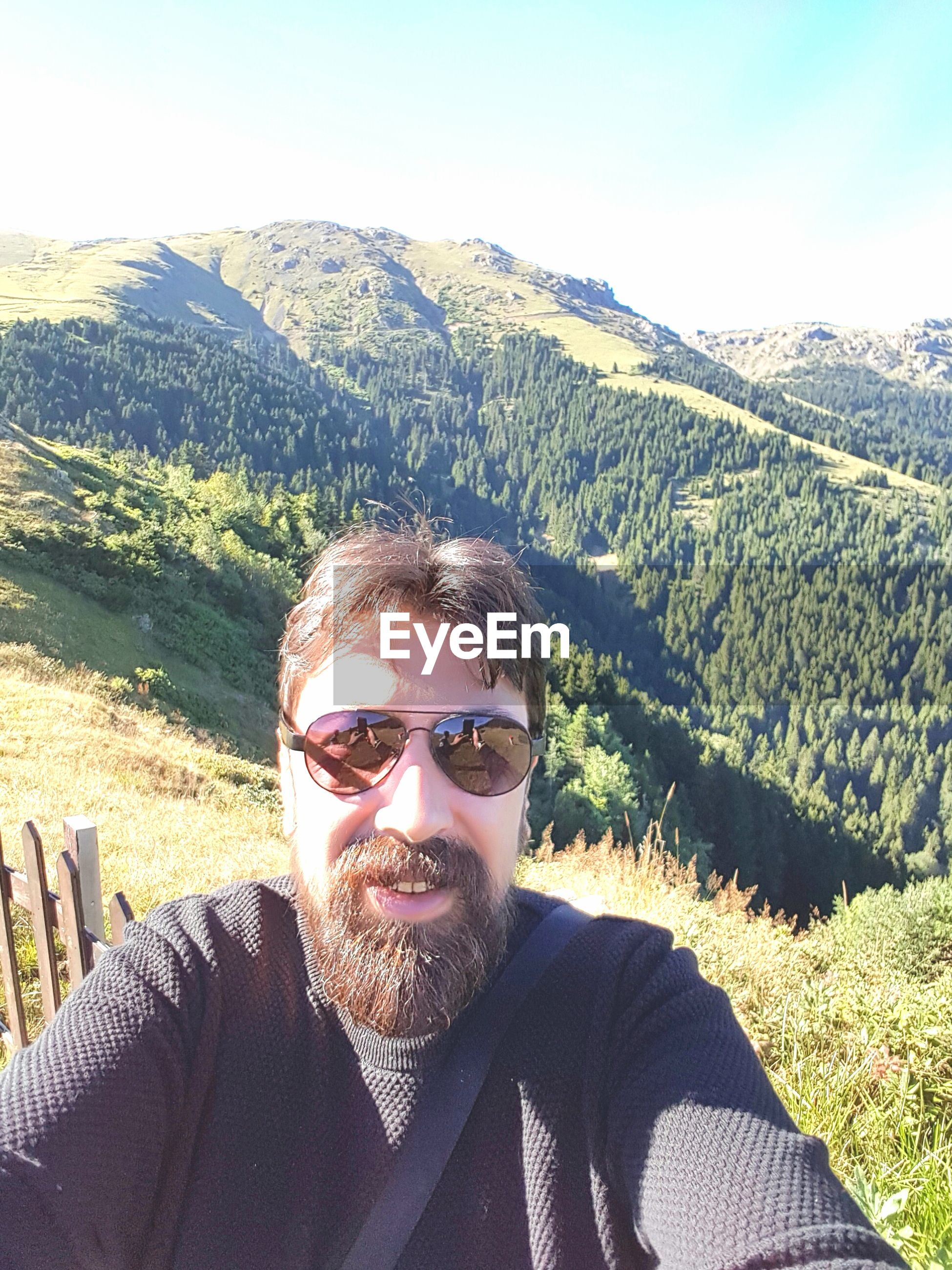Happy man taking selfie standing against mountain on sunny day