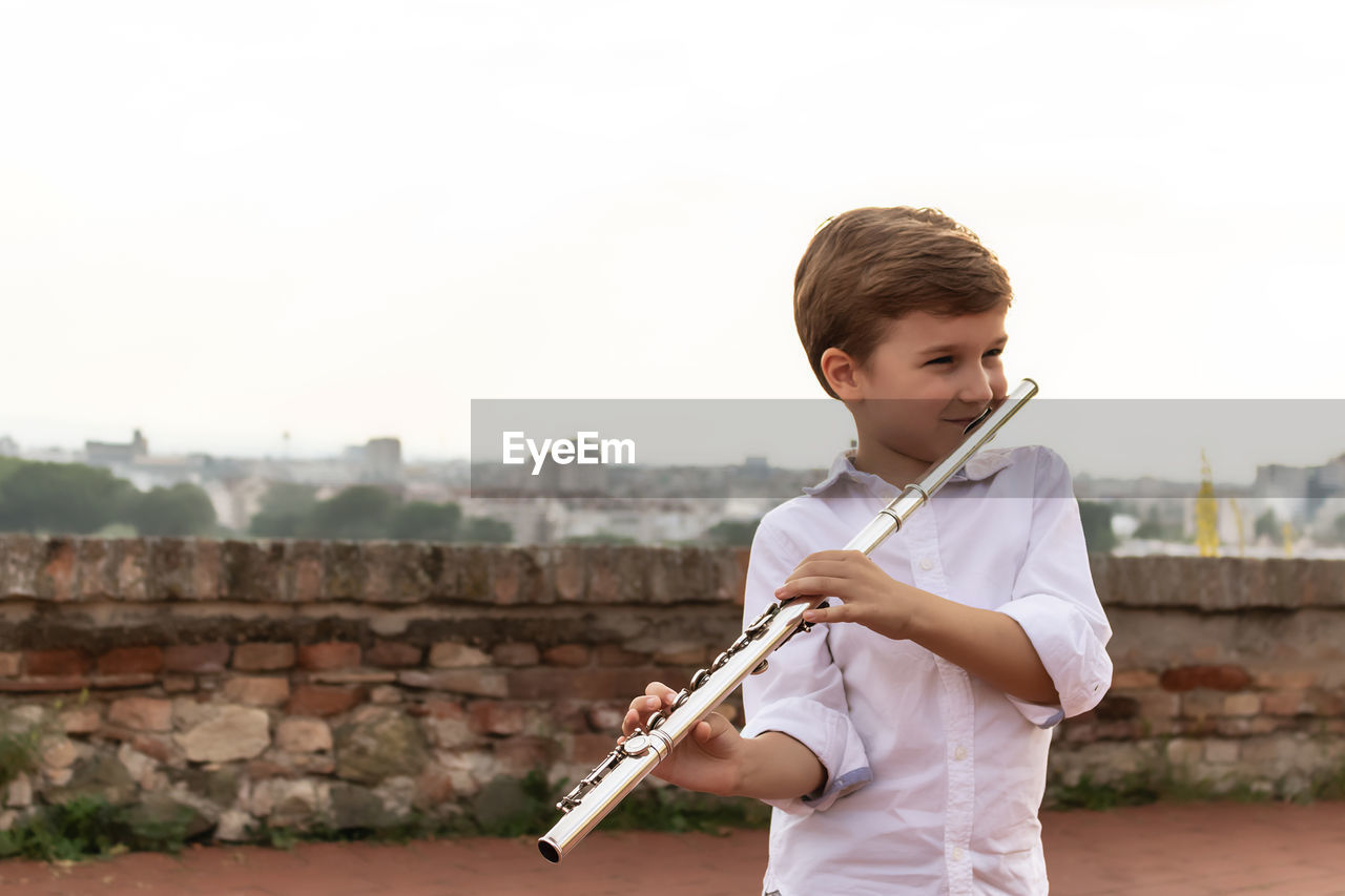 Cute little flautist playing music outdoors.