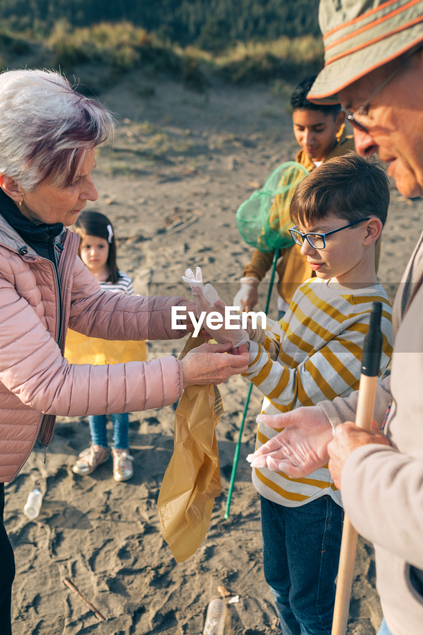 Grandmother assisting grandson while putting on protective glove while standing at beach