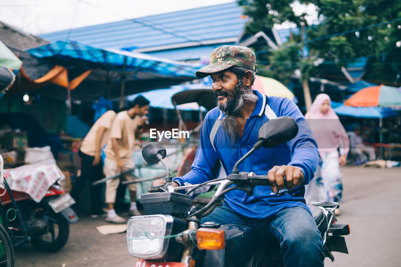 View Of Man On Motorcycle At Street Market