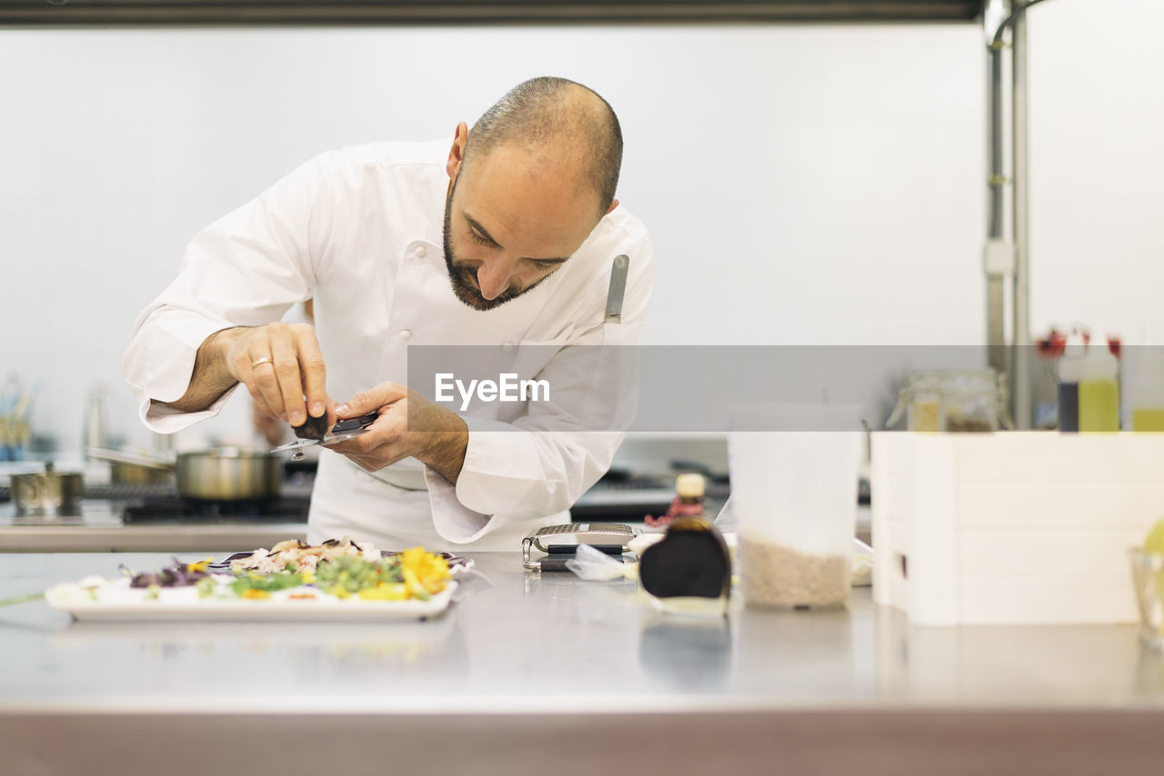 Chef garnishing food in commercial kitchen