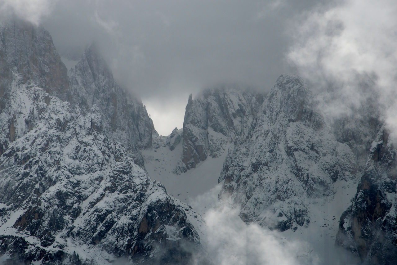 Scenic view of snowcapped alps against cloudy sky