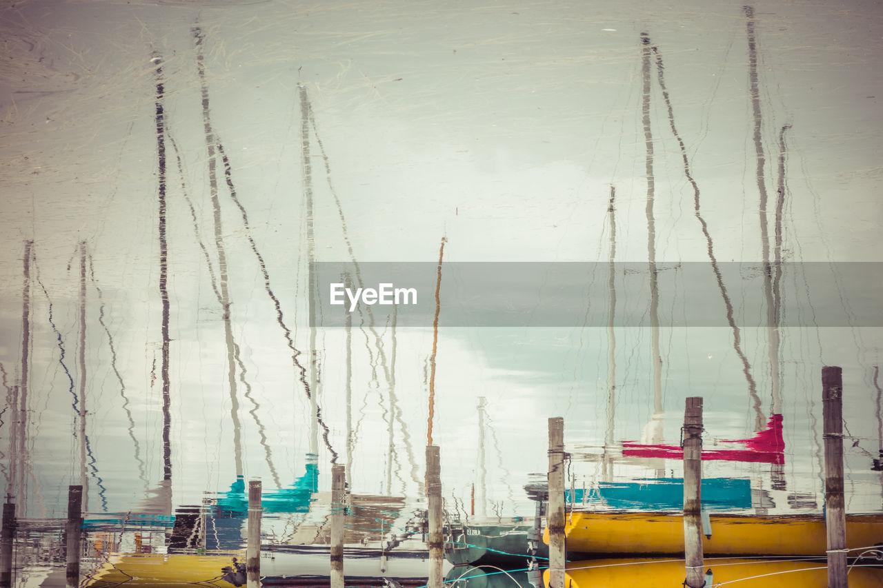 Reflection of sailboats on lake at harbor