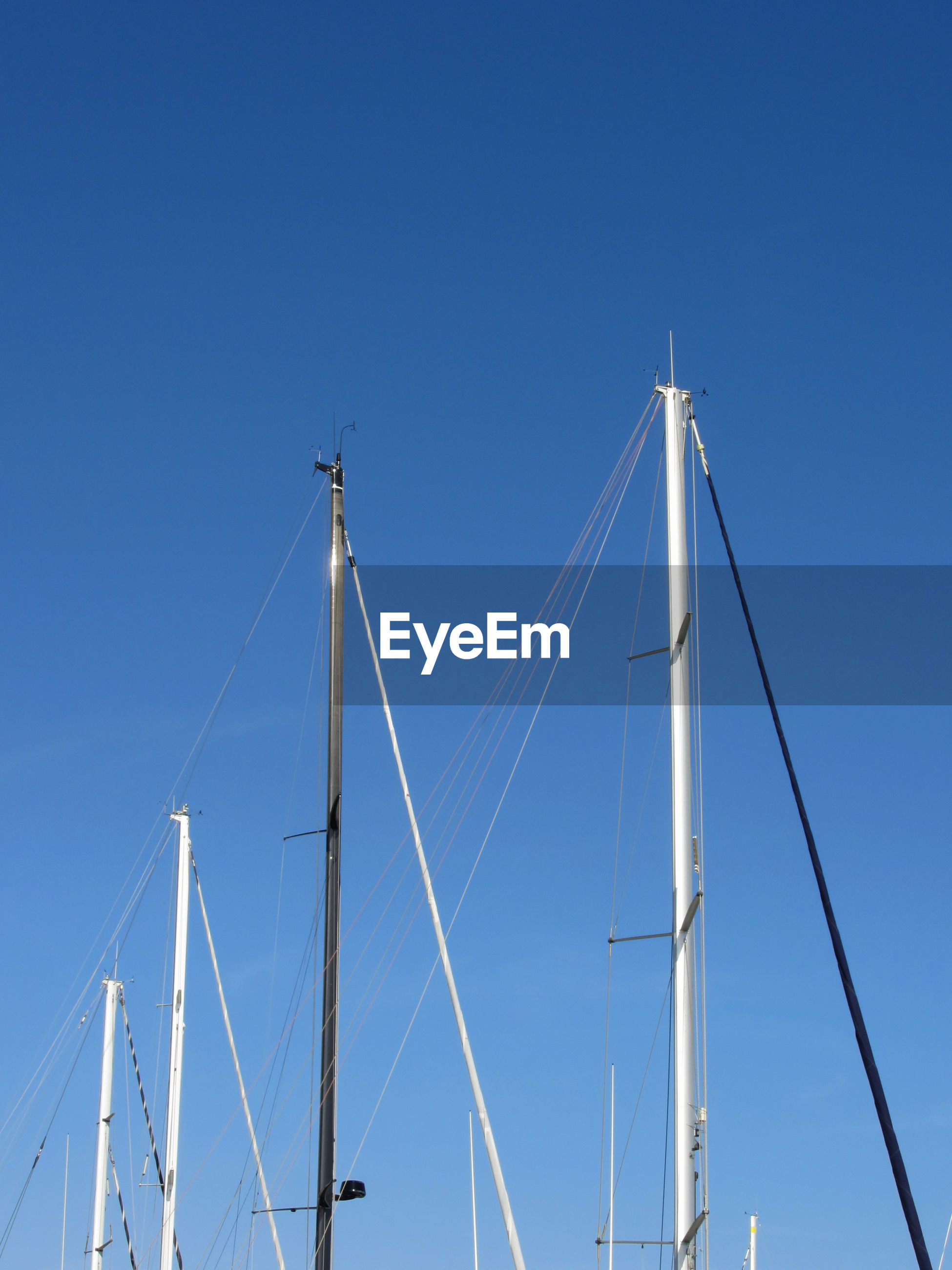 Low angle view of masts against clear blue sky
