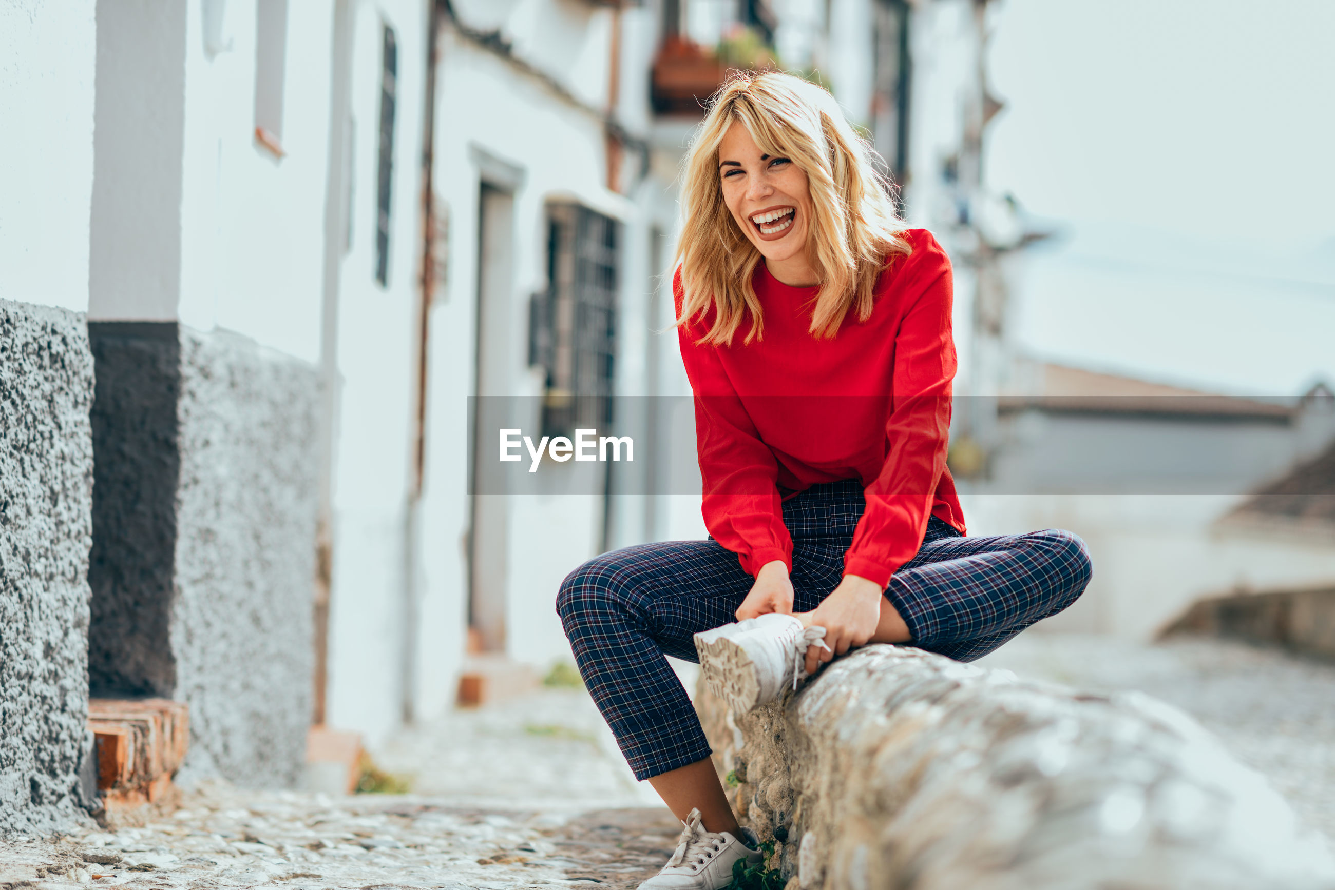Happy young woman sitting on footpath by building in city