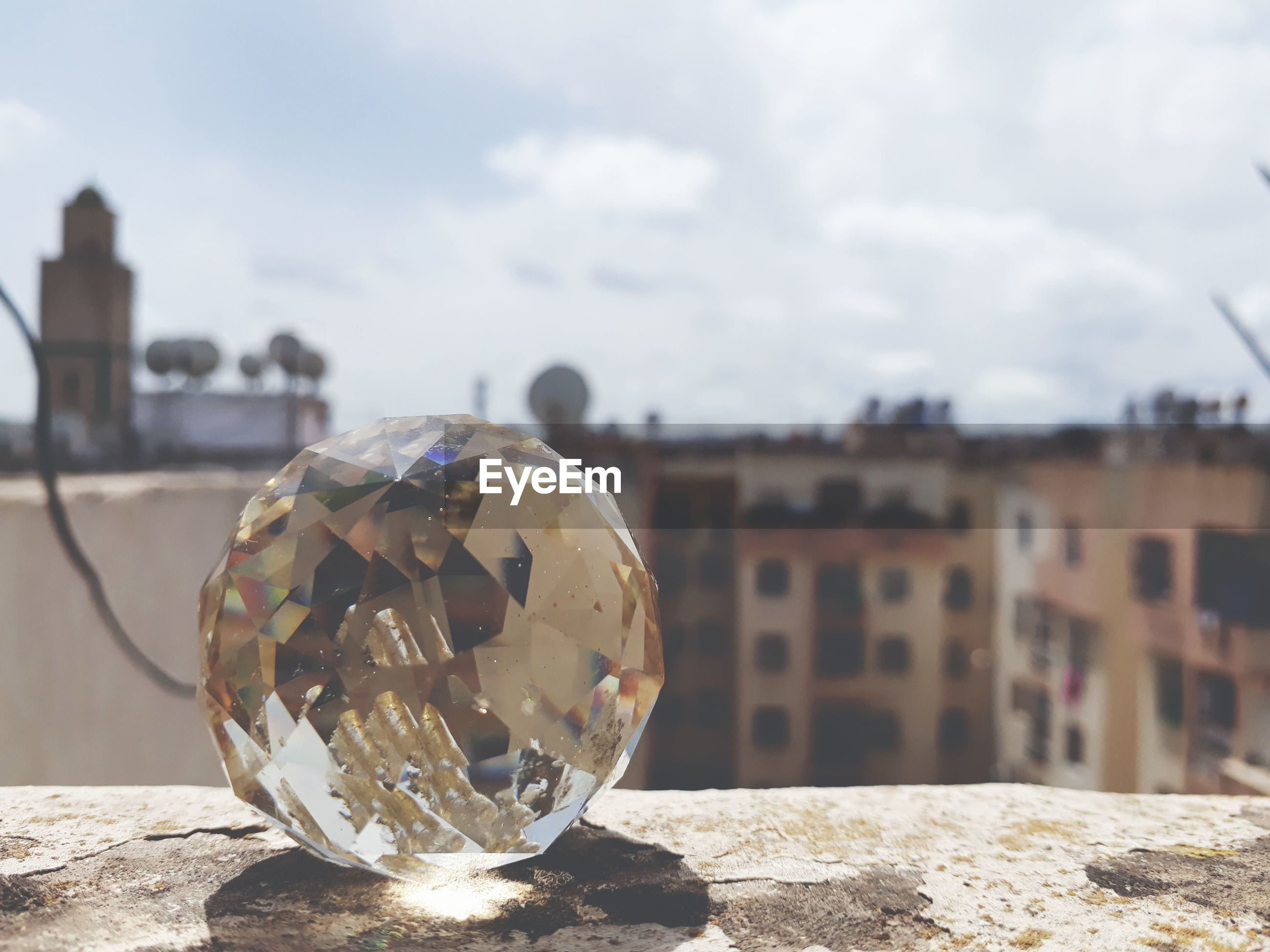 Close-up of crystal ball on land against sky in city