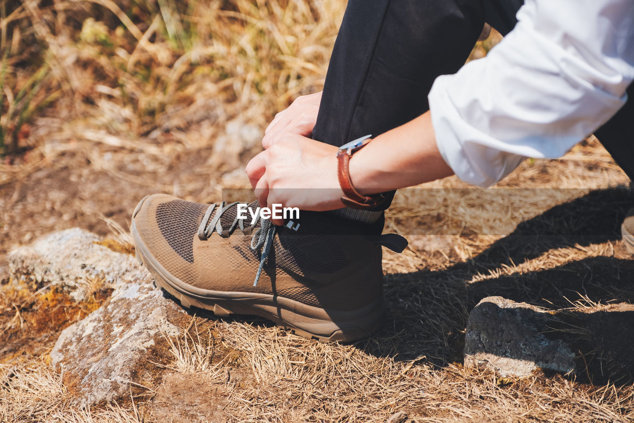 High angle view of woman tying shoelace