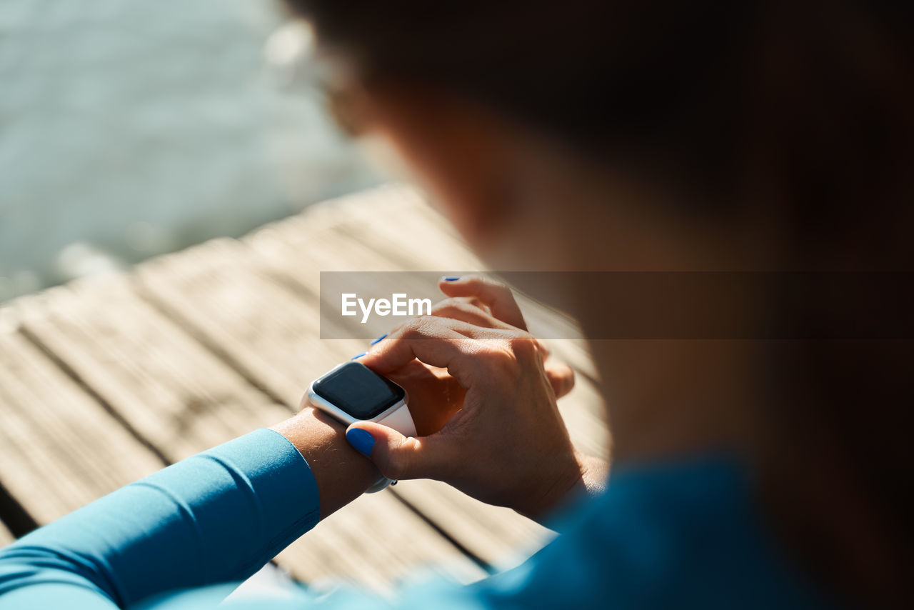 CLOSE-UP OF WOMAN USING MOBILE PHONE OUTDOORS
