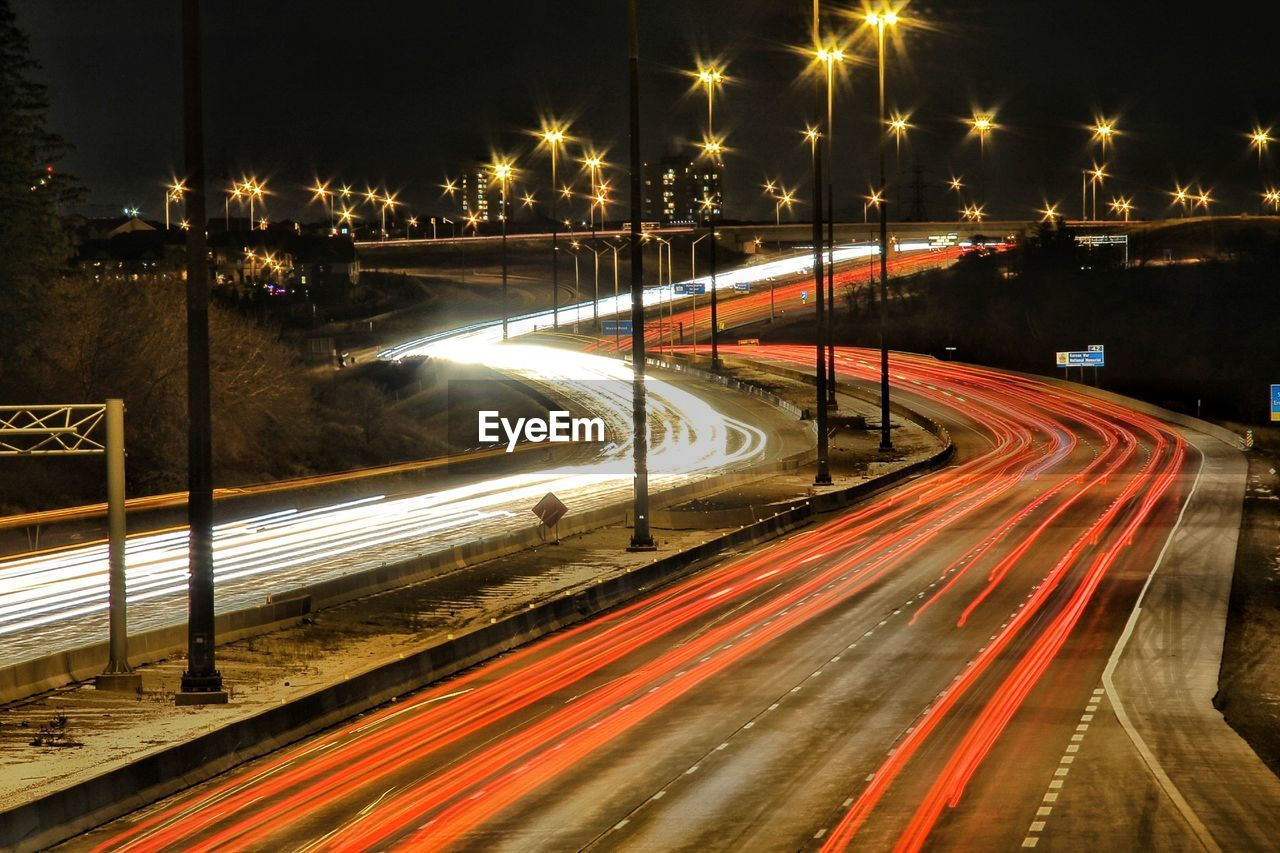 night, long exposure, light trail, illuminated, street, transportation, motion, city, speed, blurred motion, road, street light, no people, traffic, mode of transportation, architecture, high angle view, lighting equipment, red, tail light, outdoors, multiple lane highway, vehicle light