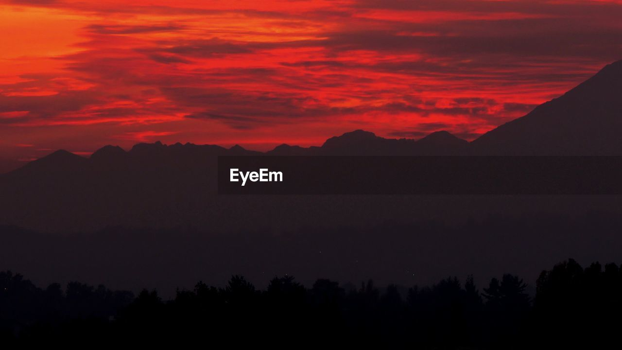 Scenic View Of Silhouette Mountains Against Dramatic Red Sky At Sunset