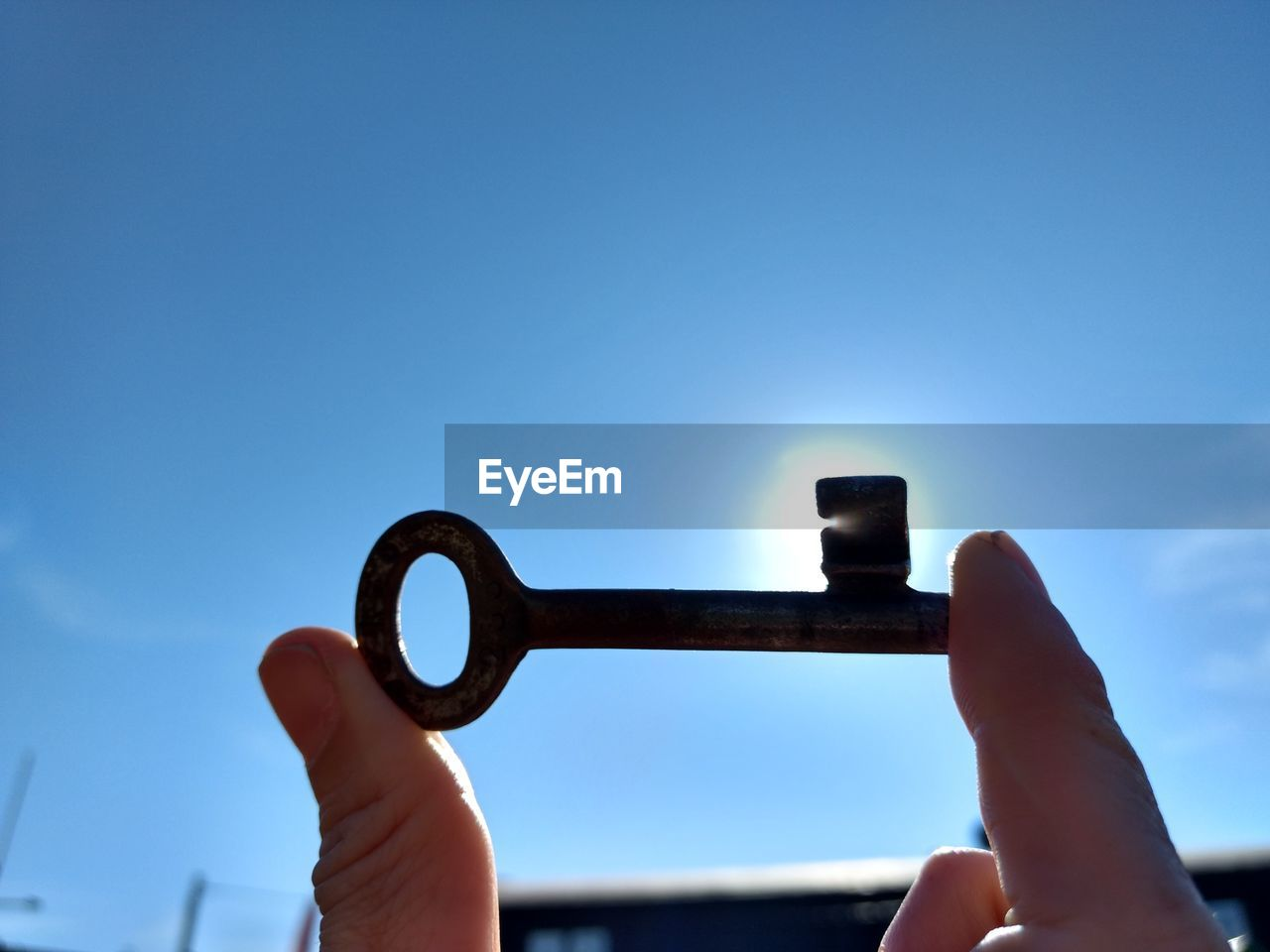 Close-up of hand holding old key against blue sky