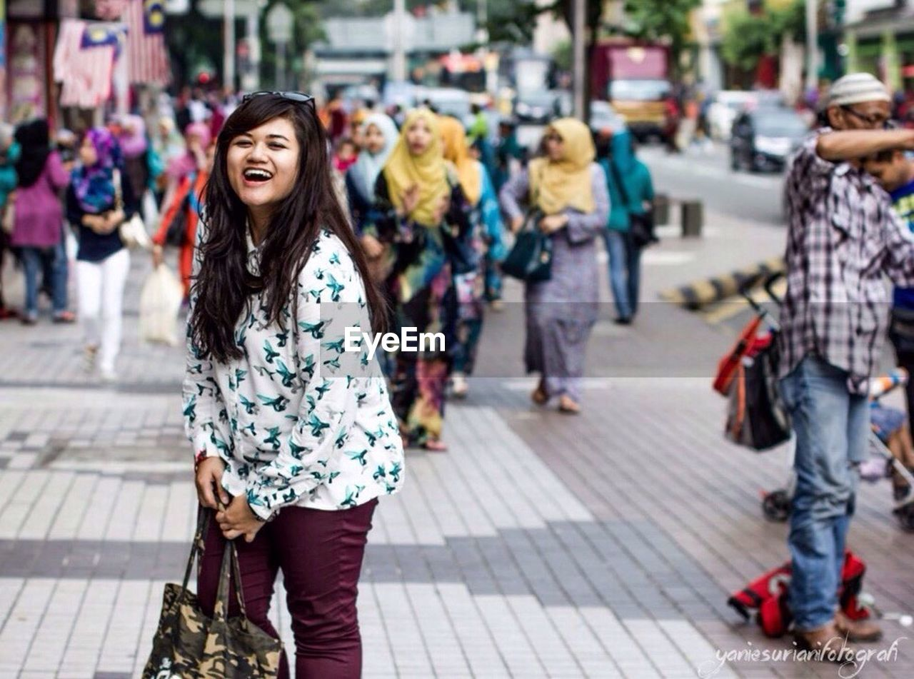incidental people, focus on foreground, outdoors, day, walking, smiling, full length, looking at camera, one person, happiness, women, portrait, pedestrian, adult, city, people, young adult, close-up, adults only