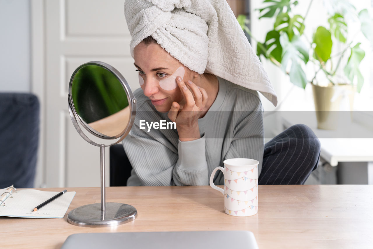 Woman applying beauty product on front of mirror on table