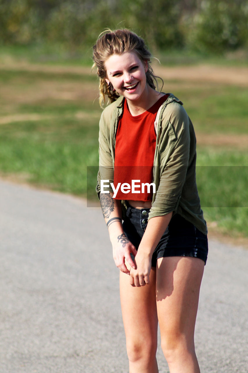 real people, young adult, young women, one person, casual clothing, leisure activity, happiness, three quarter length, lifestyles, smiling, outdoors, day, road, beautiful woman, standing, grass, nature