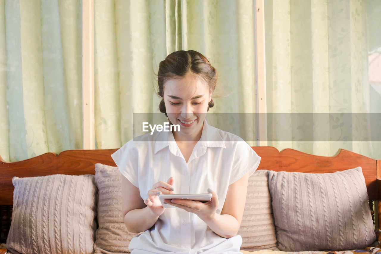 Young woman using digital tablet while sitting on sofa at home