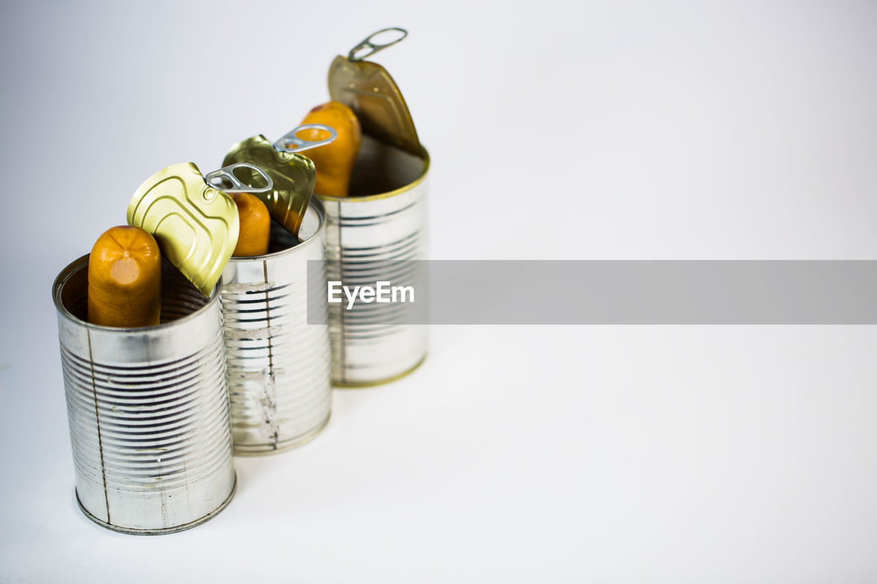 copy space, still life, indoors, studio shot, white background, no people, close-up, metal, large group of objects, food, food and drink, table, container, selective focus, business, high angle view, yellow, finance, coin, stack, silver colored, canned food