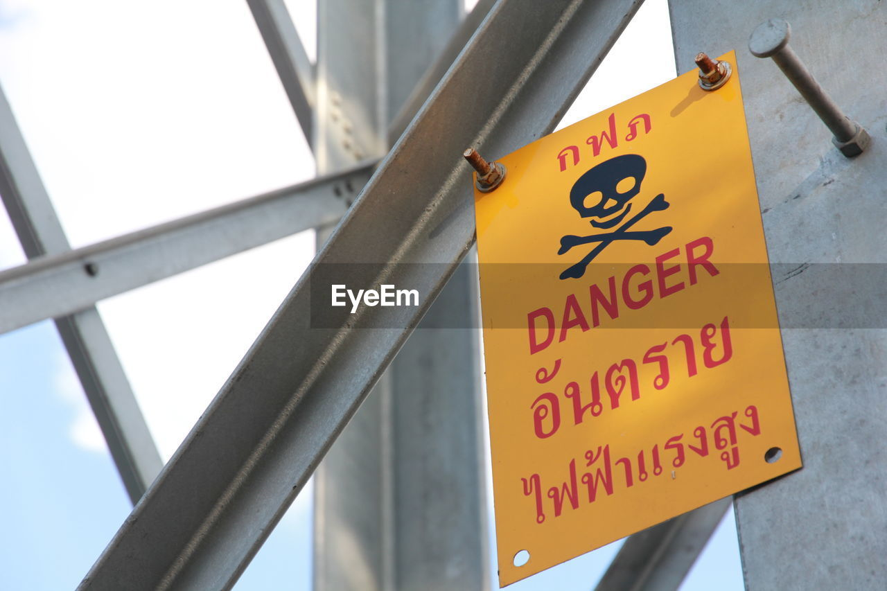 text, communication, sign, western script, yellow, warning sign, close-up, no people, day, low angle view, guidance, metal, safety, information, information sign, outdoors, script, architecture, focus on foreground, non-western script, message