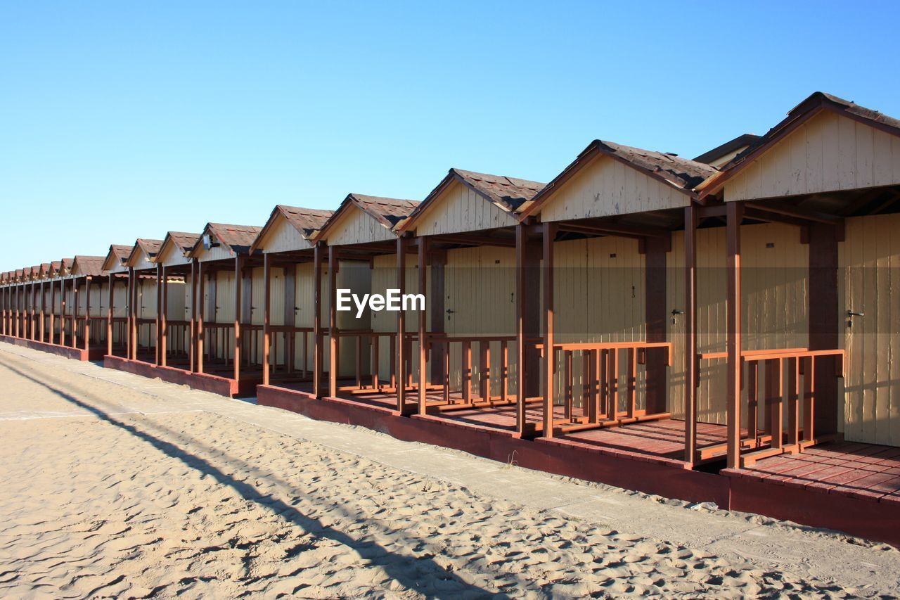 sky, built structure, clear sky, architecture, building exterior, nature, day, no people, land, in a row, sunlight, sand, beach, building, outdoors, blue, copy space, wood - material, hut, side by side