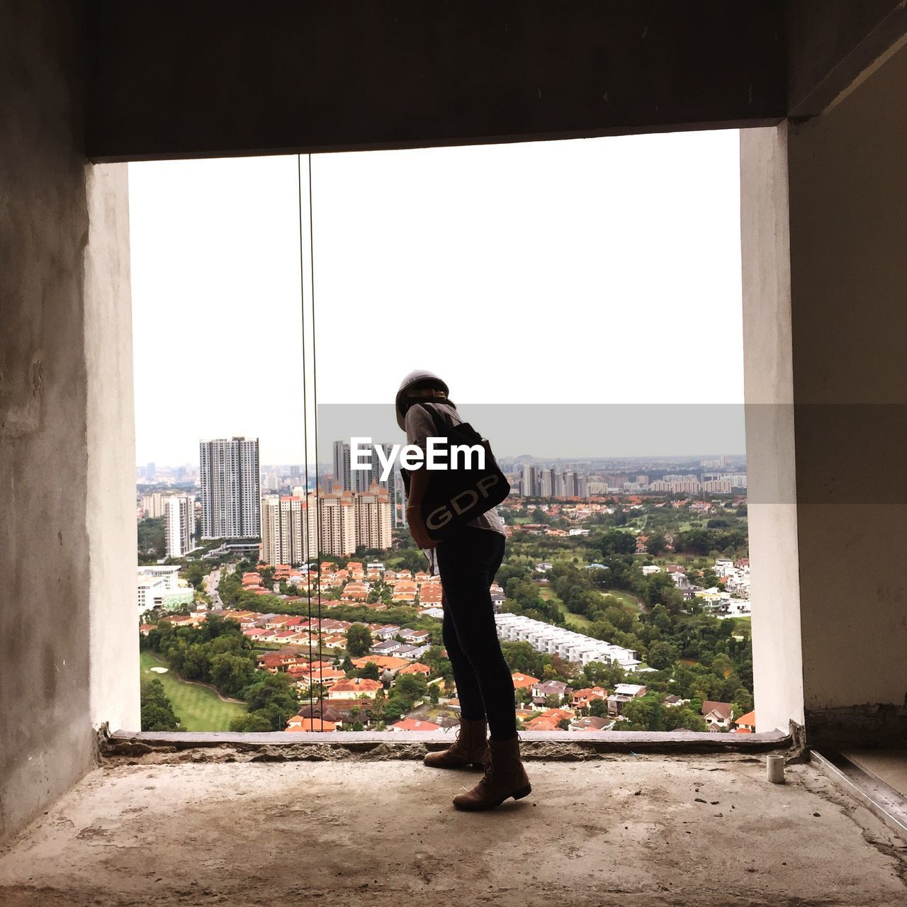 Woman Looking Down From Window In Incomplete Building