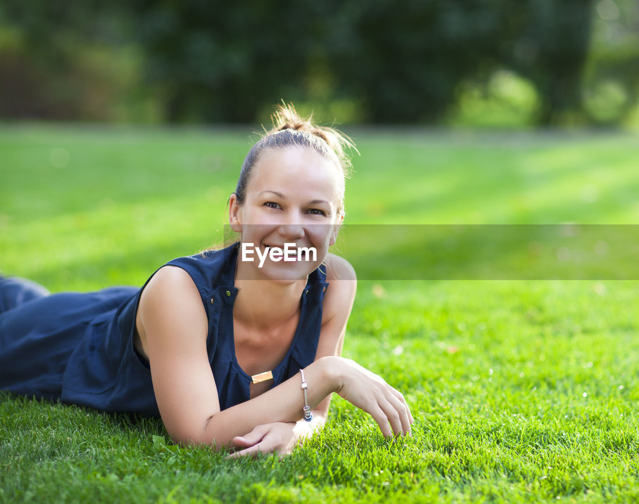 PORTRAIT OF SMILING WOMAN LYING ON GRASS