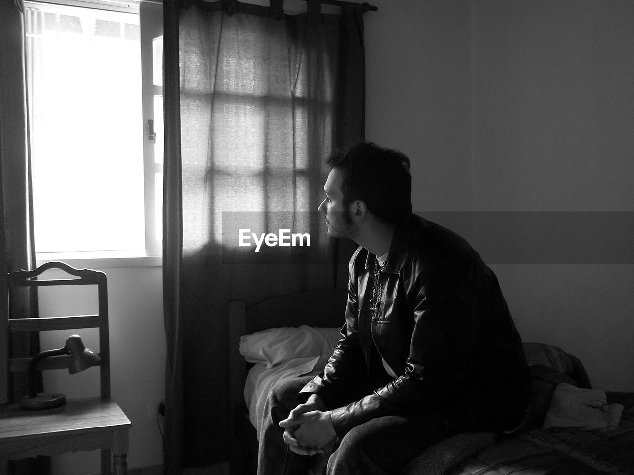 Side view of man sitting on bed looking out the window