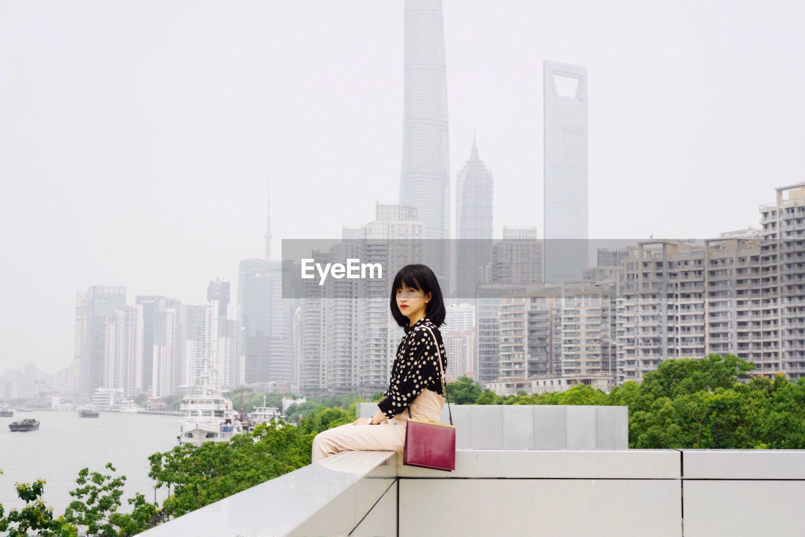 Portrait of woman sitting on buildings terrace against sky