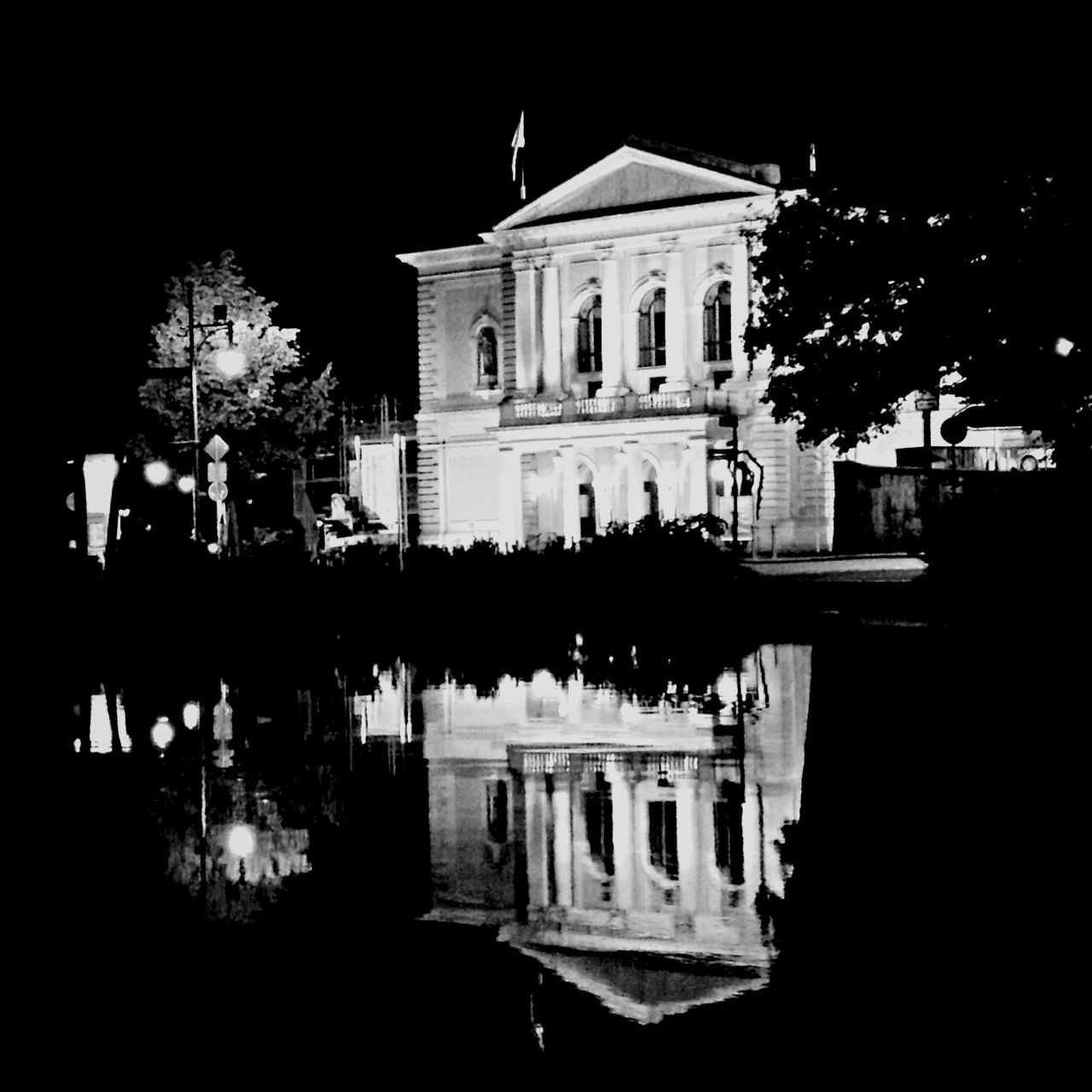 Reflection of building and trees in lake at night