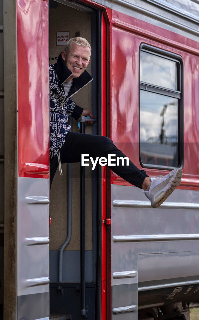 Full length of a man standing in a train with the lifted leg