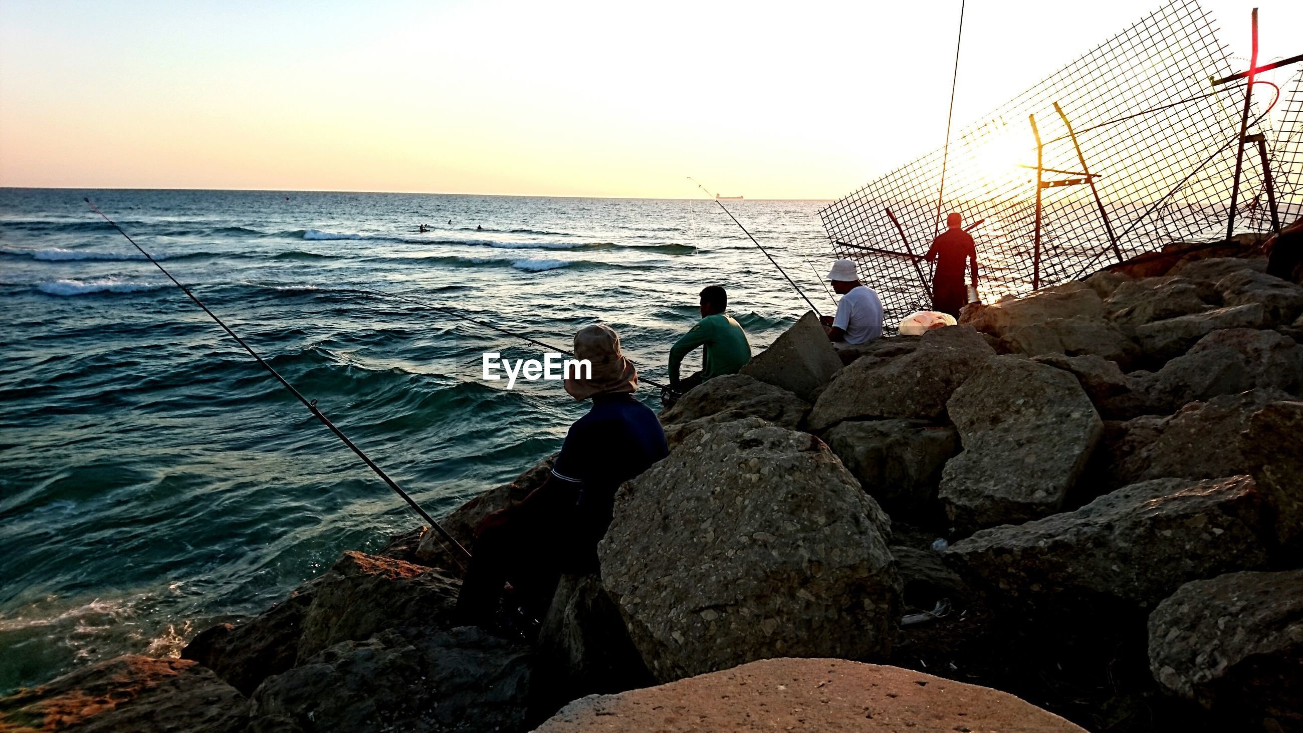 People fishing at sea shore against clear sky