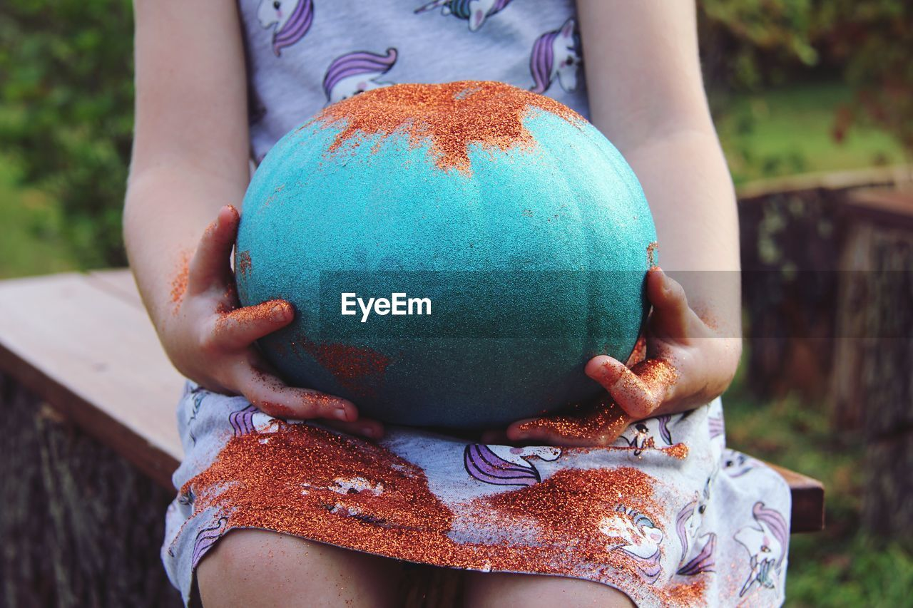 Close-Up Of Girl Holding Painted Pumpkin