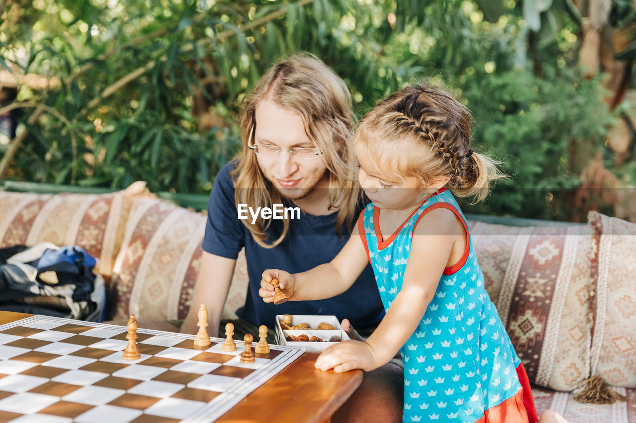 Father playing chess with daughter